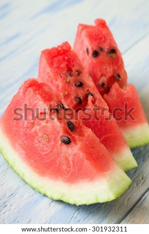 Vertical photo of three slices of fresh red water melon with visible seeds and green white peel on the bottom. Portions are placed on light blue wooden board table. - stock photo