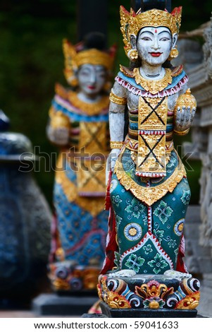 Vertical photo of two beautiful Balinese statues - stock photo