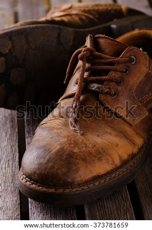 Vertical photo of two old worn brown leather shoes with damaged laces. Pair of boots is placed on grey wooden board. One boot is spilled.  - stock photo