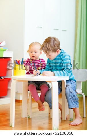 Vertical photo of two small kids drawing together at their room - stock photo