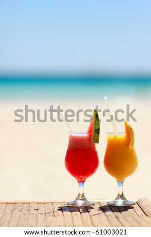 Vertical photo of two tropical fresh juices at tropical beach - stock photo