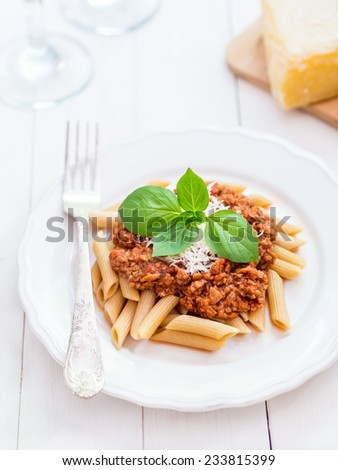 Vertical photo of whole grain penne pasta with vegetarian Bolognese sauce and Parmesan cheese, with basil leaves on the top, served on white plate with rustic fork, placed on white wooden table. - stock photo