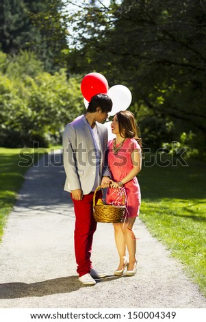 Vertical photo of young adult couple dressed in formal attire looking at each other while holding several balloons, picnic basket with walking path, green grass and trees behind them   - stock photo