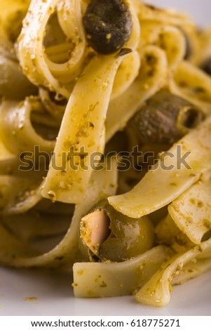 Vertical photo single portion of tagliatelle pasta with green pesto on white ceramic plate. The black and green olives with almonds are spilled around. Few capers used too.