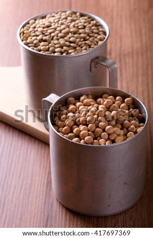 Vertical photo. Two aluminum cups. Old cups with lentils and chickpeas. Legumes in old cups. Cups on brown wooden board. One cup on wooden chopping board. Chickpeas and lentils.  - stock photo