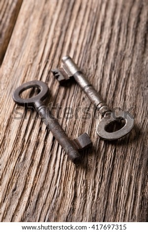 Vertical photo. Two old keys. Old keys placed on wooden board. Wooden board with worn surface. Dark photos. Board from planks. Keys from metal. Keys with rusty surface.  - stock photo