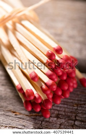 Vertical photo with Bunch of long wooden matchsticks with red heads which are bonded by piece of yellow dry straw. Bunch is placed on old worn wooden board with grey color. - stock photo
