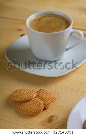Vertical photo with three lemon biscuits placed on light wooden board in front of cup of creamy coffee on square saucer. - stock photo
