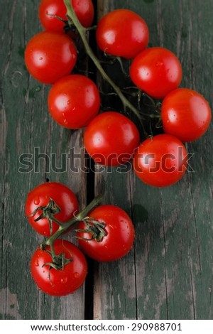 Vertical photo with top view on green worn table and placed two branches of harvested red cherry tomatoes joined by green branch. - stock photo