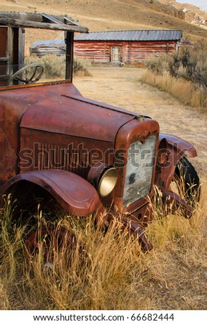 Vertical photograph of an old rusted truck sitting in dry field of grass near a Montana ghost town. - stock photo