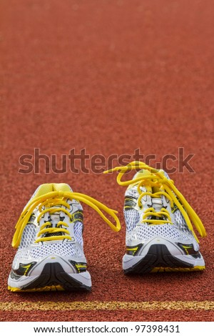 Vertical picture of a pair of runners on red tartan surface - stock photo