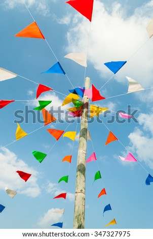 Vertical picture of colorful festive bunting flags against, on blue and clouds sky in Thailand - stock photo