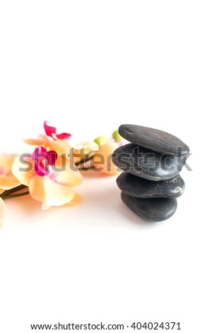 vertical picture of four stones and branches of yellow orchids on a white background - stock photo