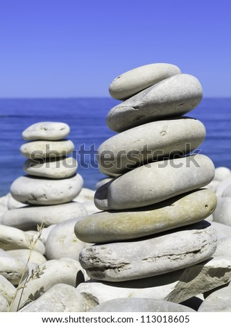 Vertical piles of smooth beach rocks by blue lake and sky (selective focus) - stock photo