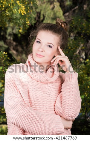 Vertical portrait of a beautiful young woman in a pink sweater in a lush garden. Knitted sweater. Fresh clean skin. A gentle smile - stock photo