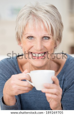 Vertical portrait of a blond short-haired Caucasian senior woman with blue eyes and a big smile looking at camera while holding a white ceramic cup - stock photo