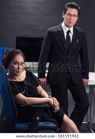 Vertical portrait of a businesswoman sitting on a chair while her colleague standing on the foreground  - stock photo
