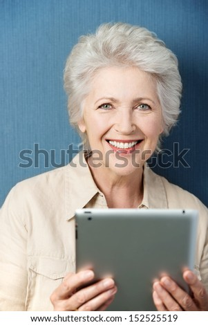 Vertical portrait of a Caucasian senior good looking woman smiling and holding a PC tablet - stock photo