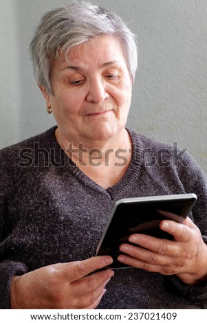 Vertical portrait of a Caucasian senior good looking woman smiling and holding a PC tablet. Grandma Using Tablet PC in Living Room - stock photo