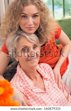 Vertical portrait of a charming grandmother and her beautiful granddaughter - stock photo