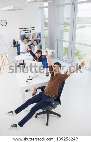 Vertical portrait of a cheerful business team with raised hands - stock photo