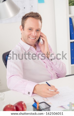 Vertical portrait of a cheerful businessman talking by smartphone and looking at camera at the office