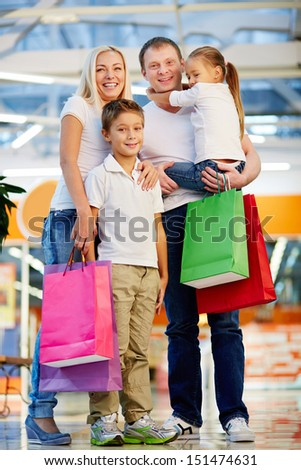 Vertical portrait of a cheerful family standing together holding shopping-bags - stock photo