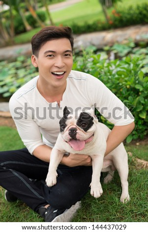 Vertical portrait of a cheerful guy hugging his pet, a French bulldog - stock photo