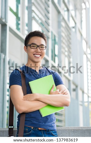 Vertical portrait of a cheerful male student standing outside - stock photo