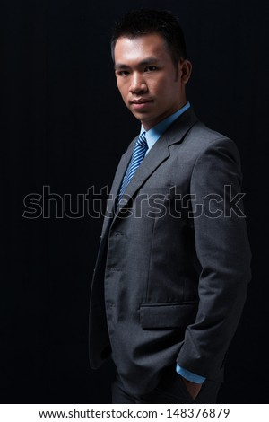 Vertical portrait of a confident young businessman over a black background