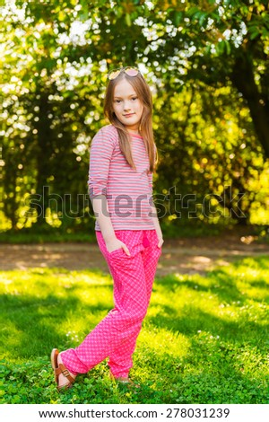 Vertical portrait of a cute little girl of 7 years old in the park - stock photo