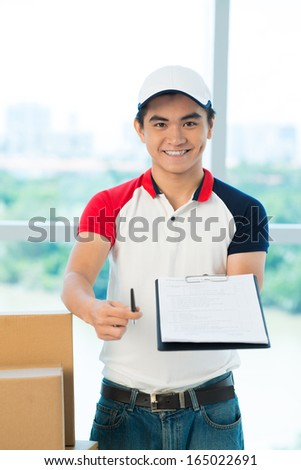 Vertical portrait of a delivery man with a confirmation form to sign - stock photo