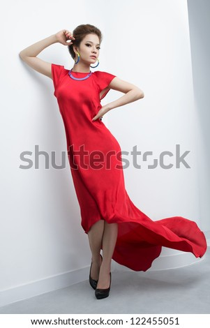 Vertical portrait of a diva posing in a fluttering red dress - stock photo