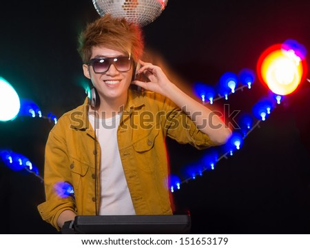 Vertical portrait of a DJ over a black background - stock photo