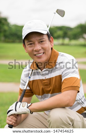 Vertical portrait of a handsome golf player with a golf-iron posing at camera - stock photo