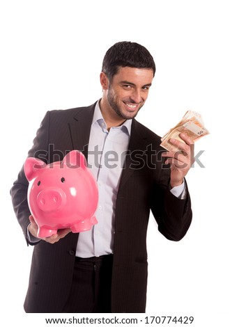 vertical portrait of a happy business man wearing a suit holding a piggy bank and money smiling at the camera on a white background