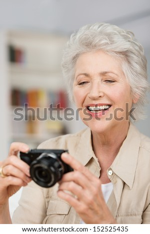 Vertical portrait of a happy caucasian senior woman setting her compact camera - stock photo