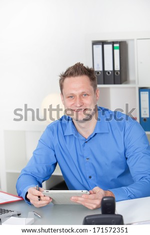 Vertical portrait of a happy Caucasian young male employee smiling while holding a new Pc tablet at his desk, in the office, with copy space