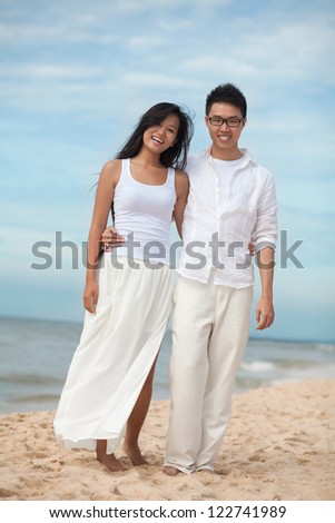 Vertical portrait of a happy couple enjoying their vocational season together - stock photo