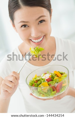 Vertical portrait of a lovely young woman eating healthy