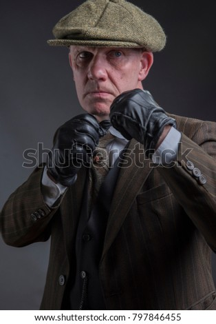 Vertical portrait of a mature gangster with his fists up ready to punch