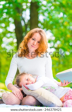 Vertical portrait of a mother and daughter in the park - stock photo