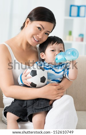 Vertical portrait of a mother holding her son while he drinking milk  - stock photo