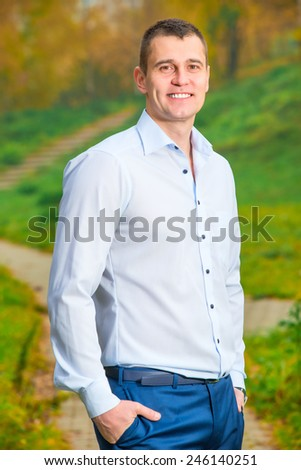 Vertical portrait of a smiling man 35 years in the park - stock photo