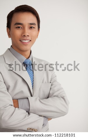 Vertical portrait of a smiling young businessman with his arms crossed confidently - stock photo