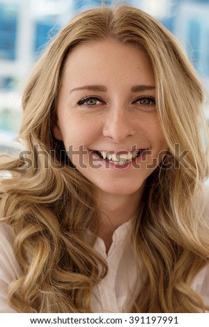 Vertical portrait of a smiling young woman, blue background