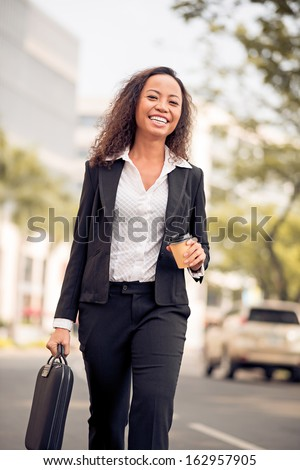 Vertical portrait of a young attractive businesswoman with a coffee on the way to work - stock photo