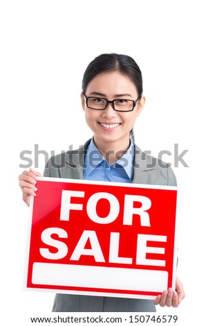 """Vertical portrait of a young attractive realtor with a """"for sale"""" placard against a white background - stock photo"""