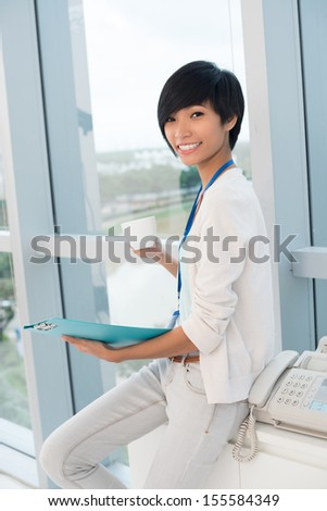 Vertical portrait of a young business lady during the tea break posing at camera