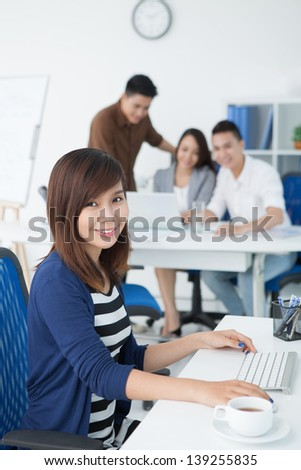 Vertical portrait of a young businesswoman at work on the foreground